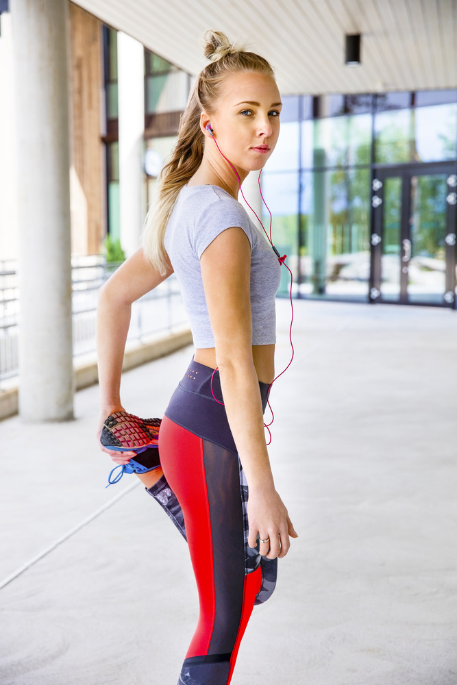 Sporty Woman Stretching Leg Before Running On Footpath