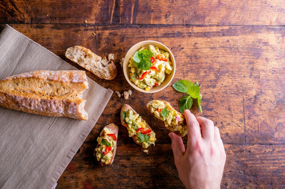 Spread made of avocado and other ingredients in a bowl and on slices of bruschetta. Hand of man taking it, eating. Studio shot on old wooden table background