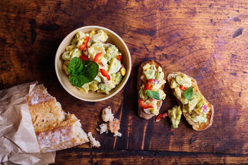 Spread made of avocado and other ingredients on slices of bruschetta. Studio shot on wooden background.