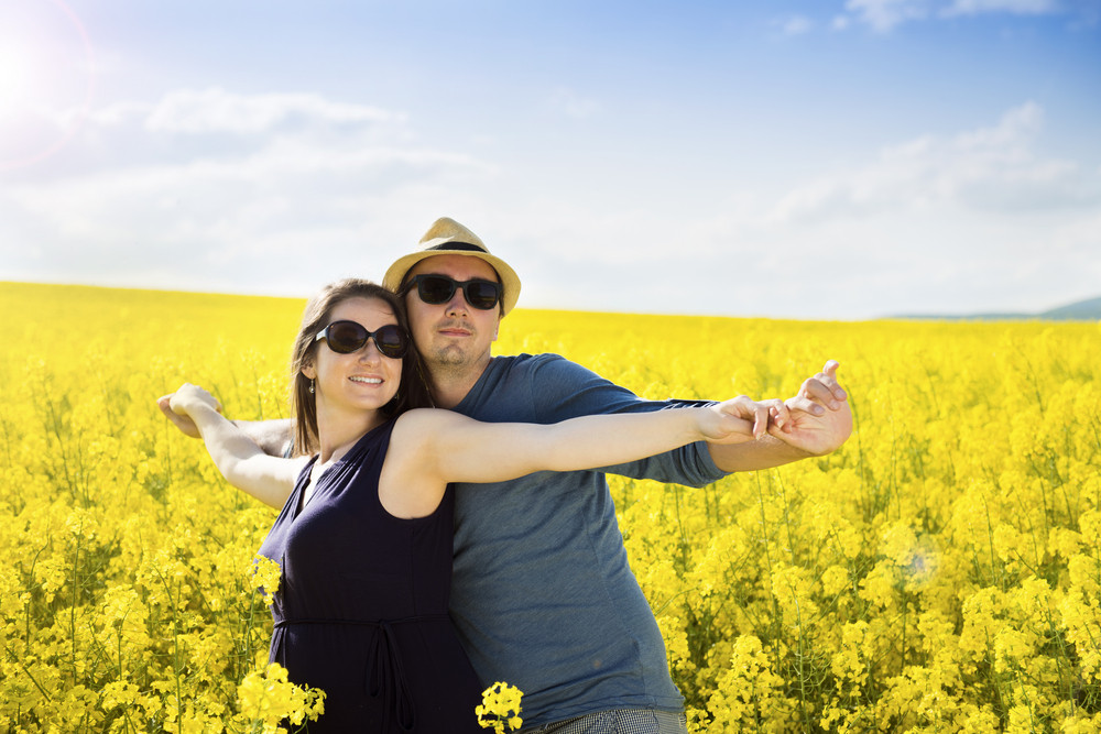Spring outdoor portrait of young pregnant couple