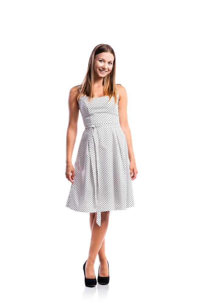 Standing teenage girl in black-and-white dotted dress, heels, legs crossed, studio shot, young woman, isolated on white background