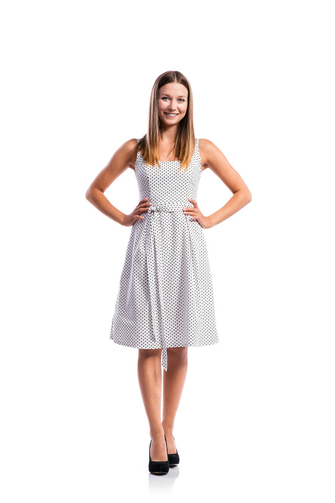 Standing teenage girl in black-and-white dotted dress, heels, studio shot, young woman, isolated on white background