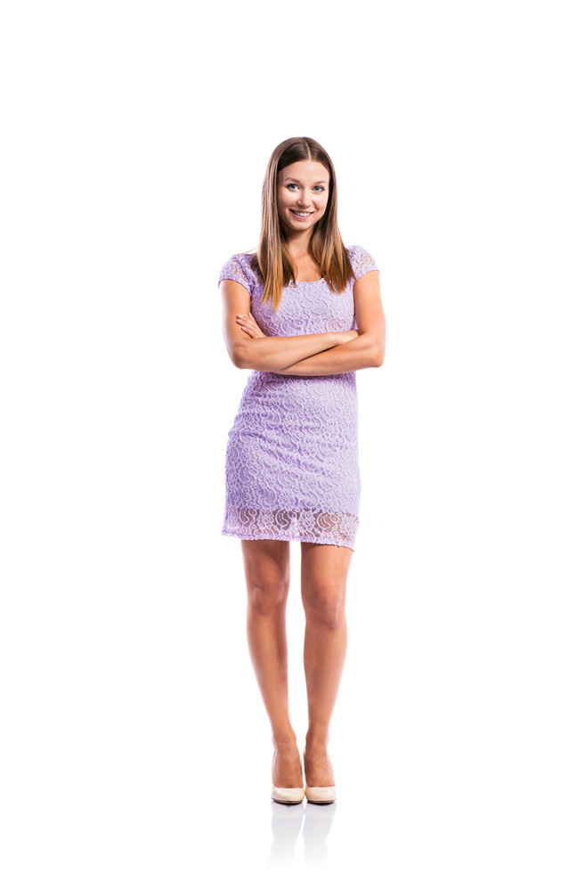 Standing teenage girl in elegant purple lace dress, heels, arms crossed, studio shot, young woman, isolated on white background