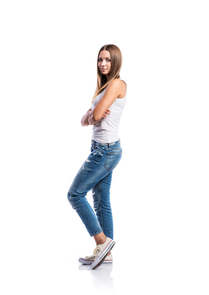 Standing teenage girl in jeans, tight singlet and sneakers, arms crossed, young woman, isolated on white background