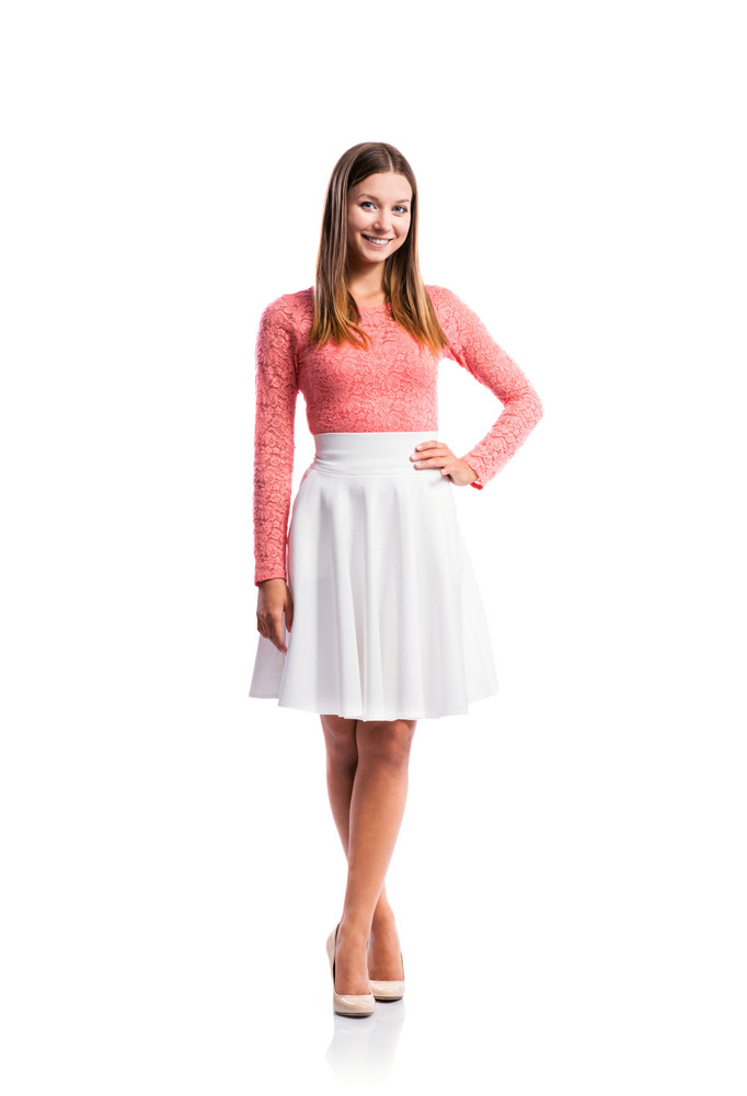 Standing teenage girl in pink lace top and elegant white skirt, heels, studio shot, young woman, arm on hip, isolated on white background