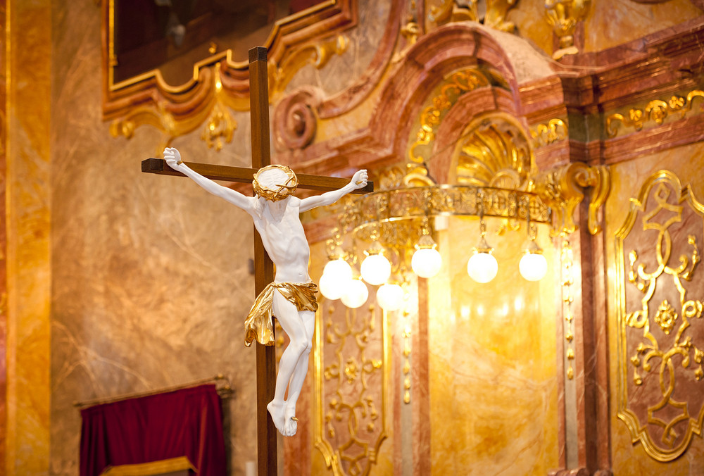 Still photo of wooden cross with Jesus Christ in church