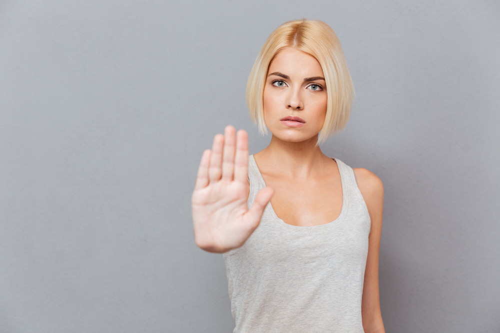 Strict serious young woman showing stop gesture over gray background