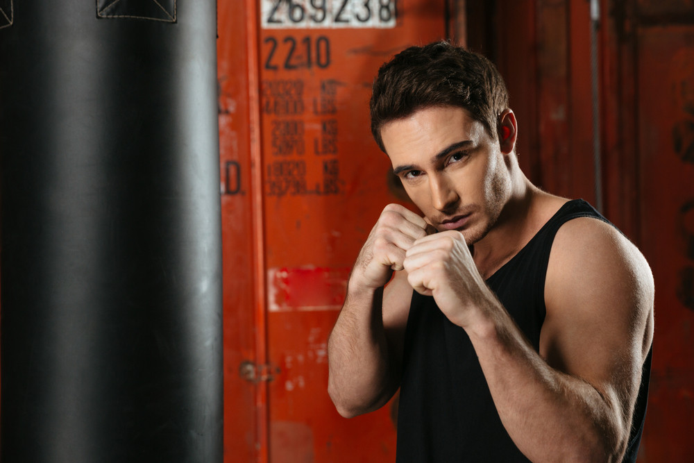 Strong boxer standing in a gym near punch bag and posing with hands. Looking at camera.