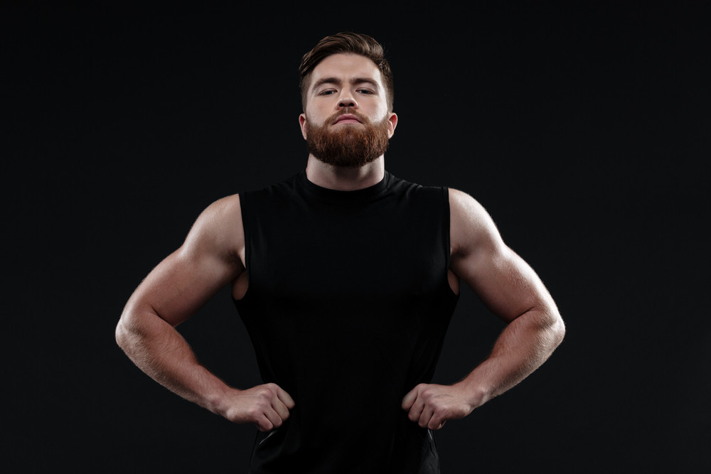 Strong trainer. arms at hips. looking at camera. isolated gray background