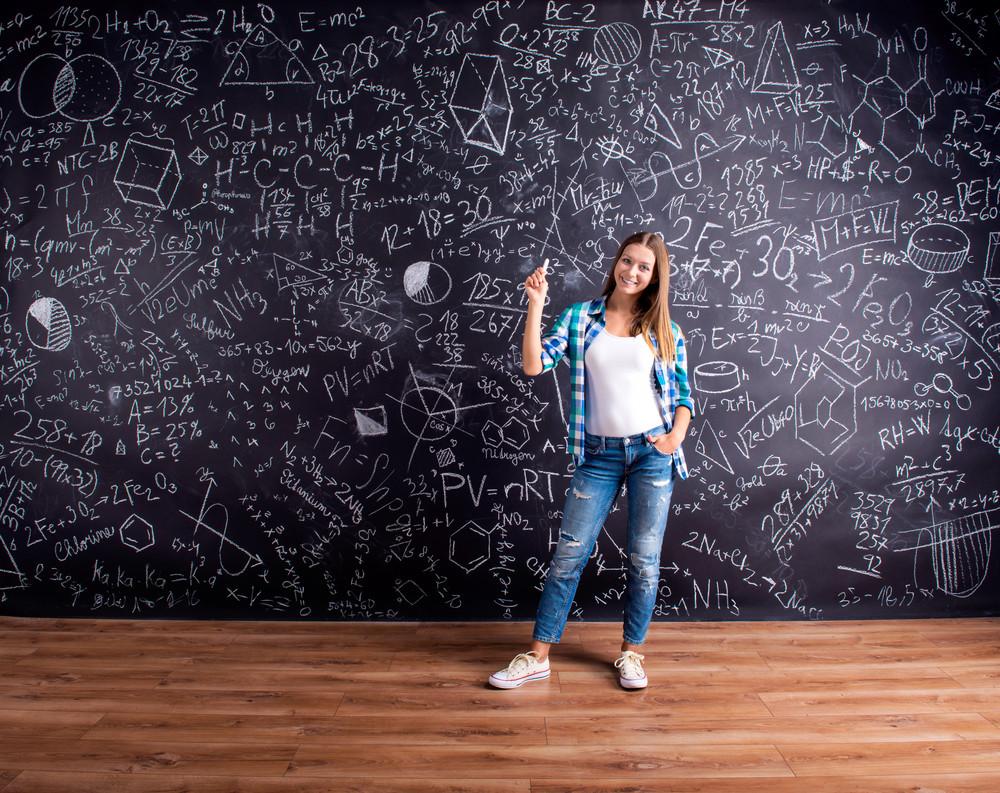 Student holding a chalk, against big blackboard with mathematical symbols and formulas. Studio shot on black background.