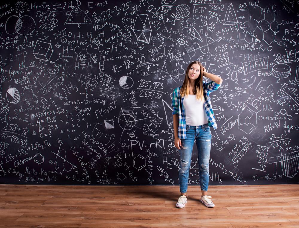 Student holding her head, thinking, against big blackboard with mathematical symbols and formulas. Studio shot on black background.