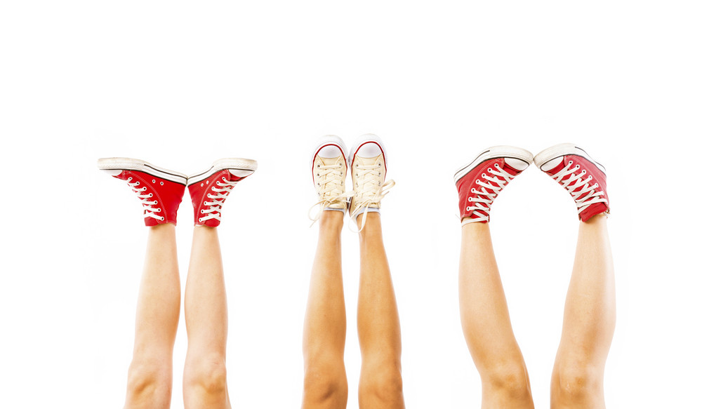 Students feet concept with sneakers on white background with space for text