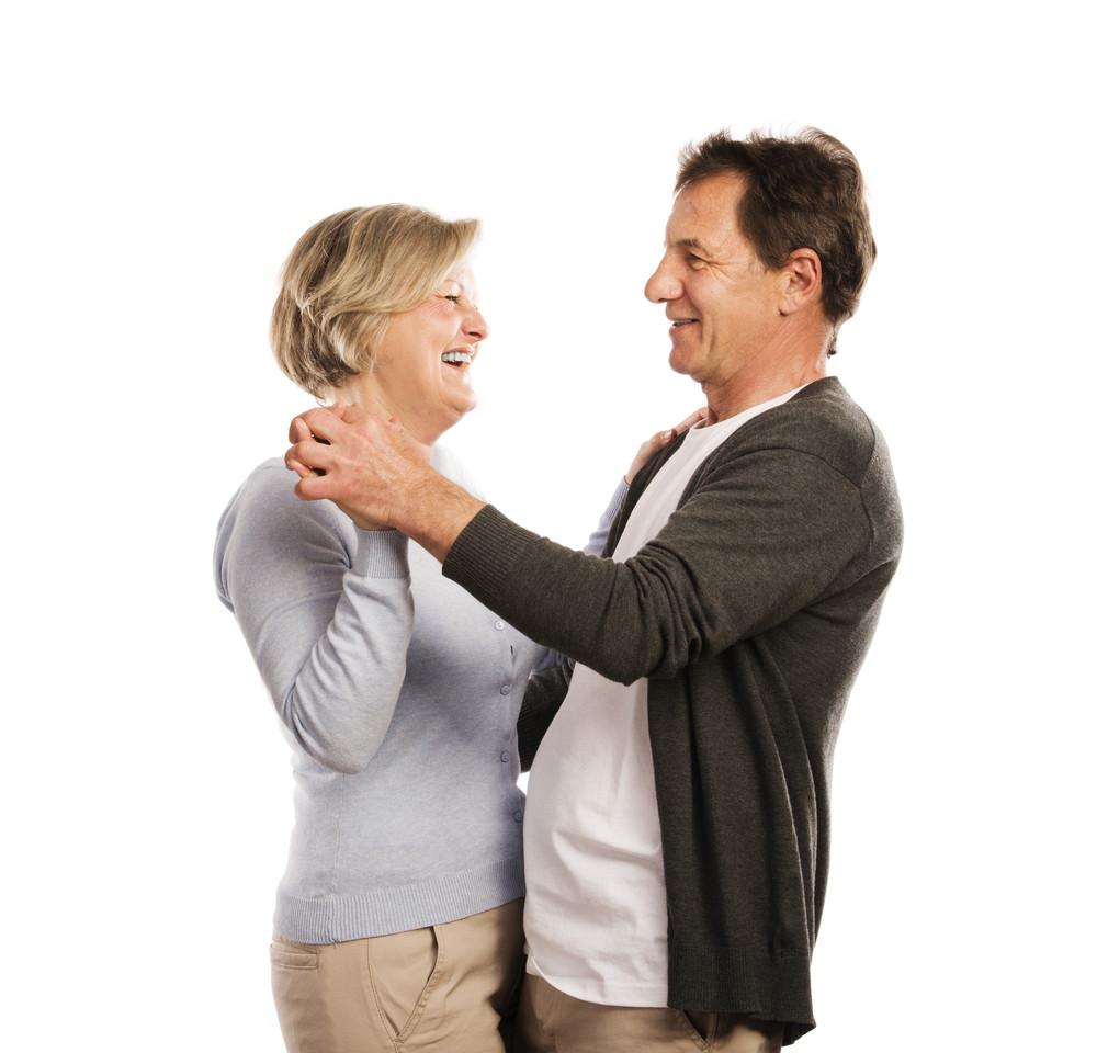 Studio portrait of happy seniors couple dancing. Isolated on white background.