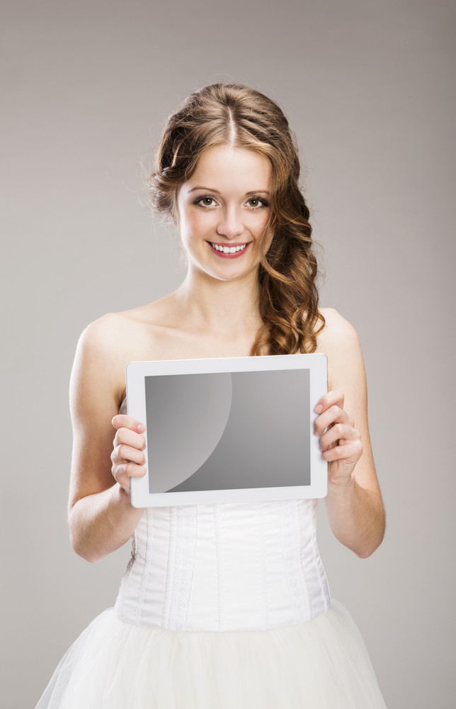 Studio portraits of beautiful bride with digital tablet isolated on gray background