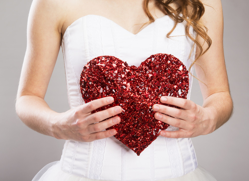 Studio portraits with beautiful bride isolated on gray background. She is holding red heart.