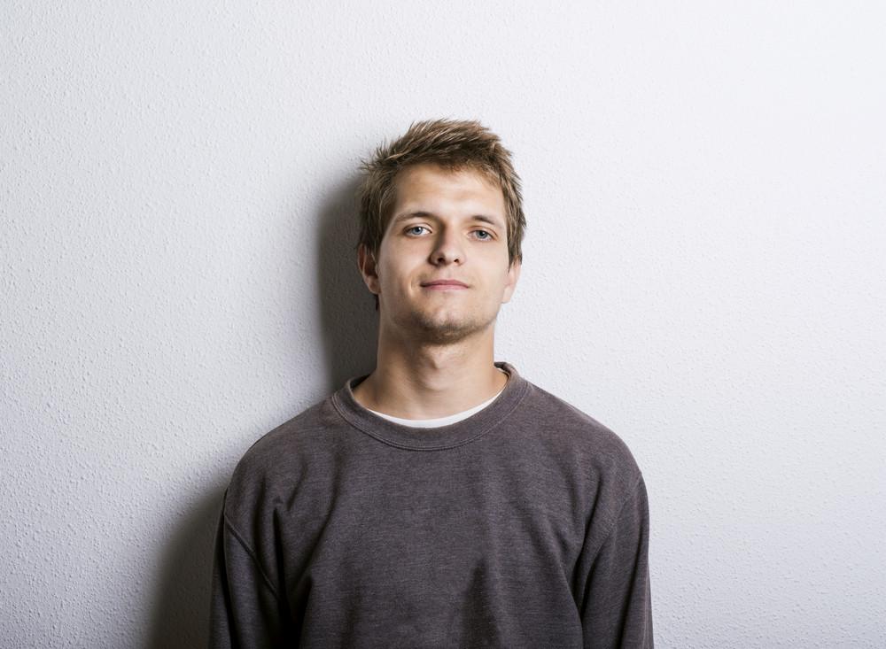 Studio shot of casual young man looking at camera