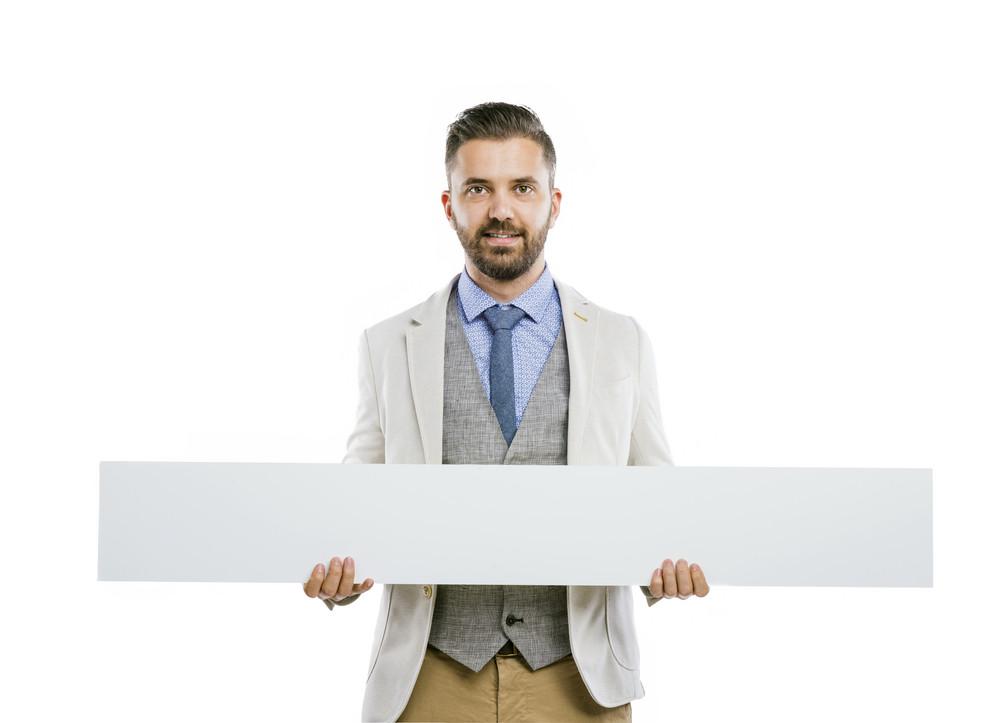 Studio shot of modern hipster businessman holding blank advertisement on black background