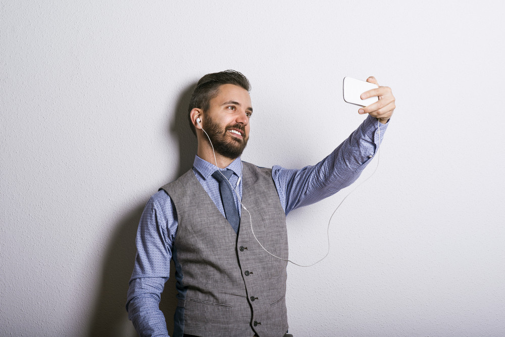 Studio shot of modern hipster businessman taking selfie with mobile phone