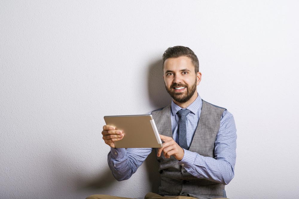 Studio shot of modern hipster businessman using digital tablet