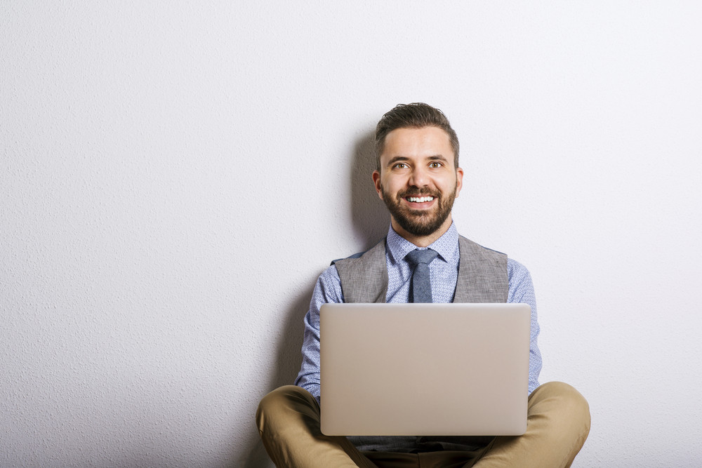 Studio shot of modern hipster businessman using laptop