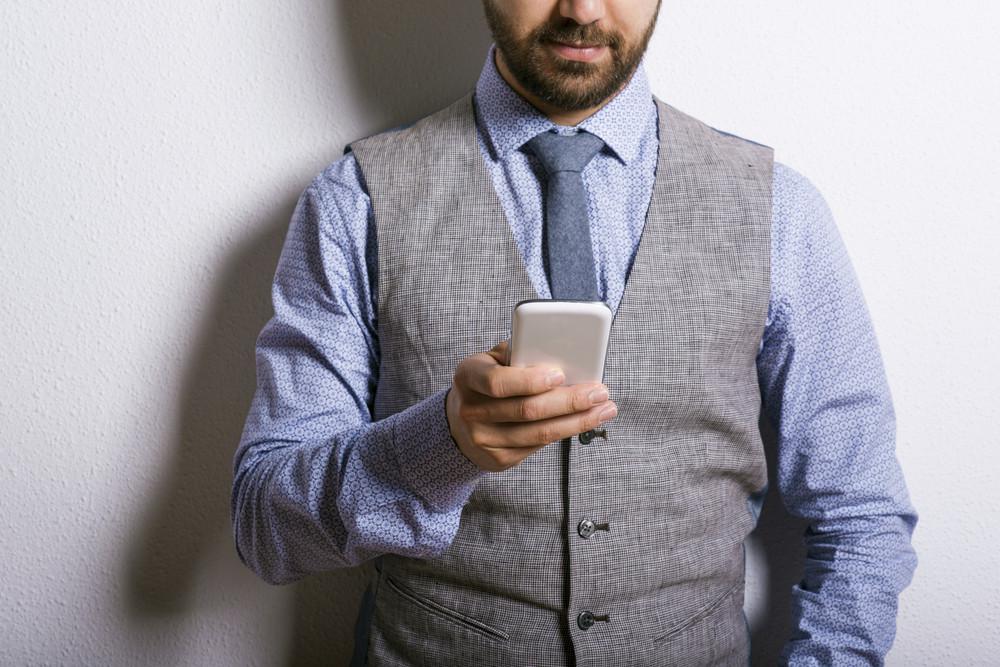 Studio shot of modern hipster businessman using mobile phone