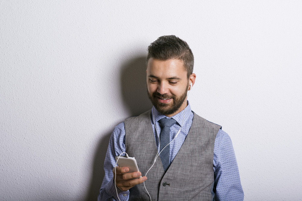 Studio shot of modern hipster businessman with headphones, listening to music from mobile phone