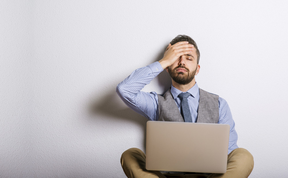 Studio shot of tired hipster businessman working on laptop