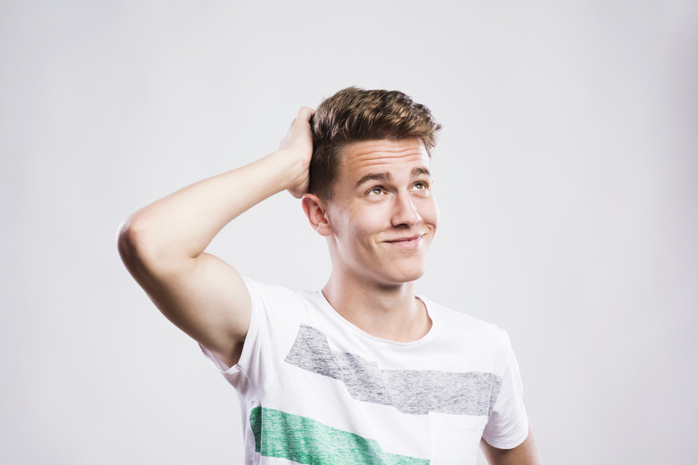 Stylish handsome young hipster posing. Studio shot on white background