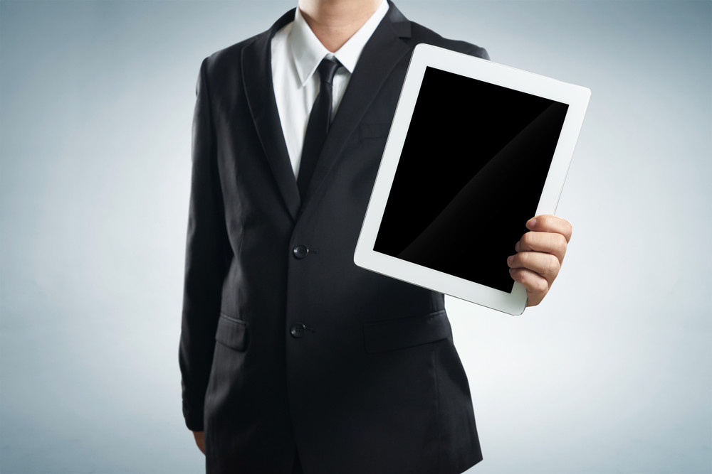 successful young businessman shows the screen of the tablet on a white background, selective focus on tablet.