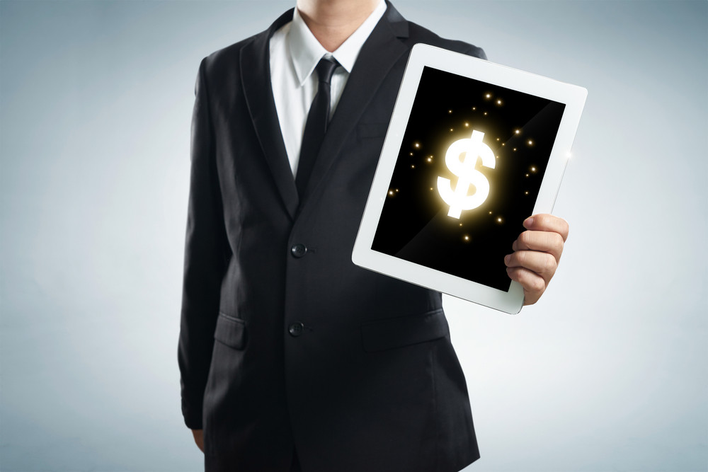 successful young businessman shows the screen of the tablet with dollar symbo