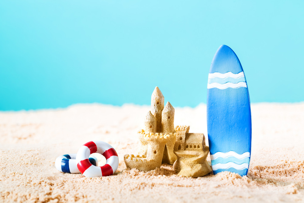Summer theme with surfboard and sand castle on a bright blue background