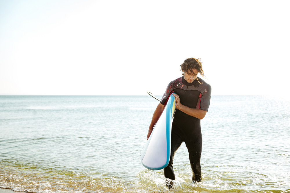 Surfer man in swimsuit walking out of the water with surf board in his hands