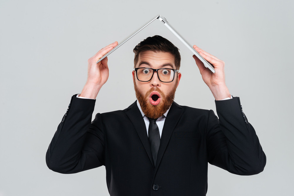 Surprised bearded business man in glasses and black suit holding laptop overhead and looking at camera. Isolated gray background