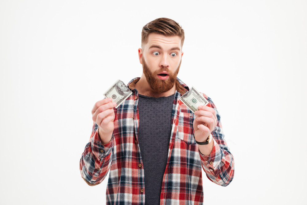 Surprised bearded man in plaid shirt holding torn banknote isolated on a white background