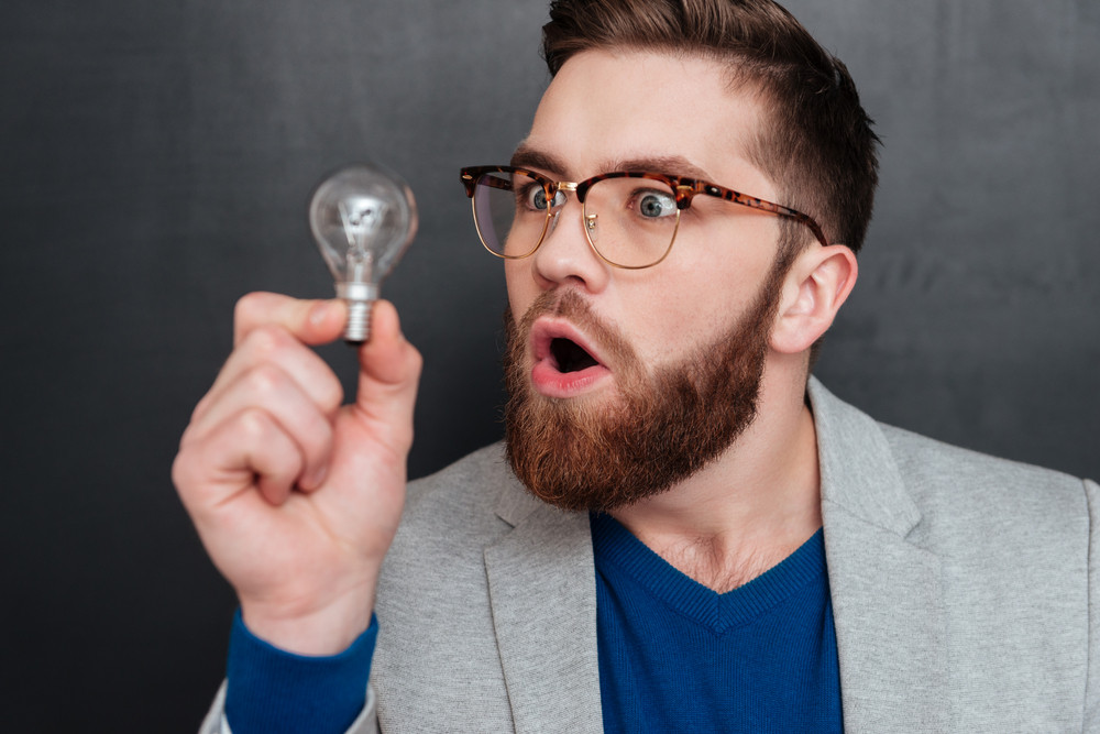 Surprised hipster with bulb in studio. looking at bulb. close up portrait. isolated black background