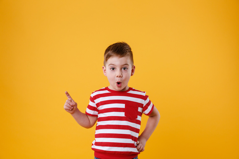 Surprised little boy standing and pointing finger away isolated over orange background