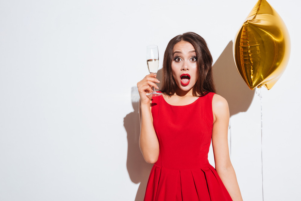 Surprised lovely young woman with star shaped balloon and glass of champagne standing over white background