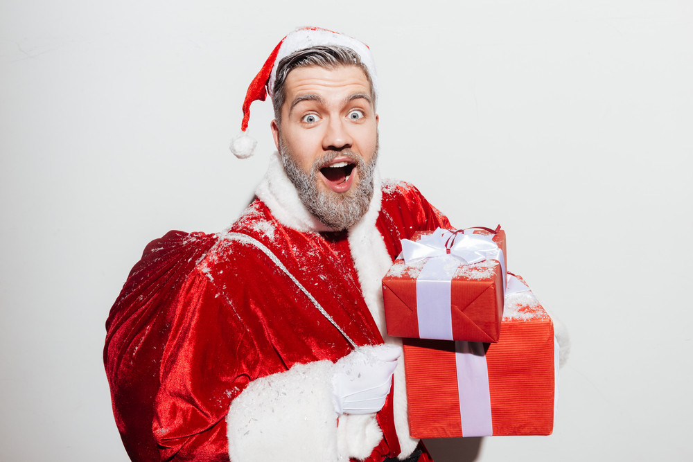Surprised man santa claus holding gift boxes and present sack