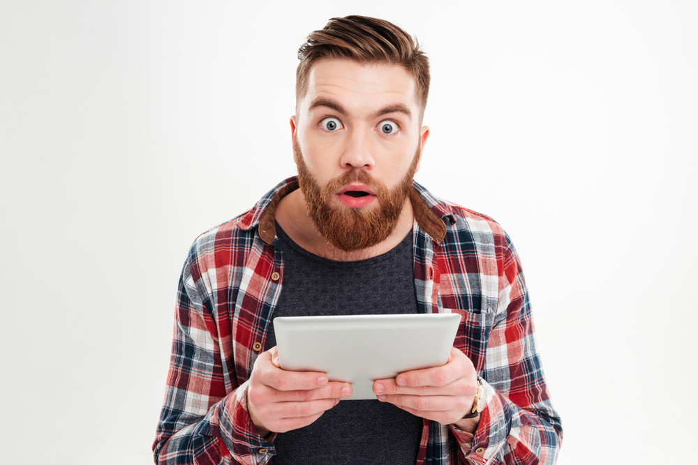 Surprised young bearded man in plaid shirt holding tablet over white background