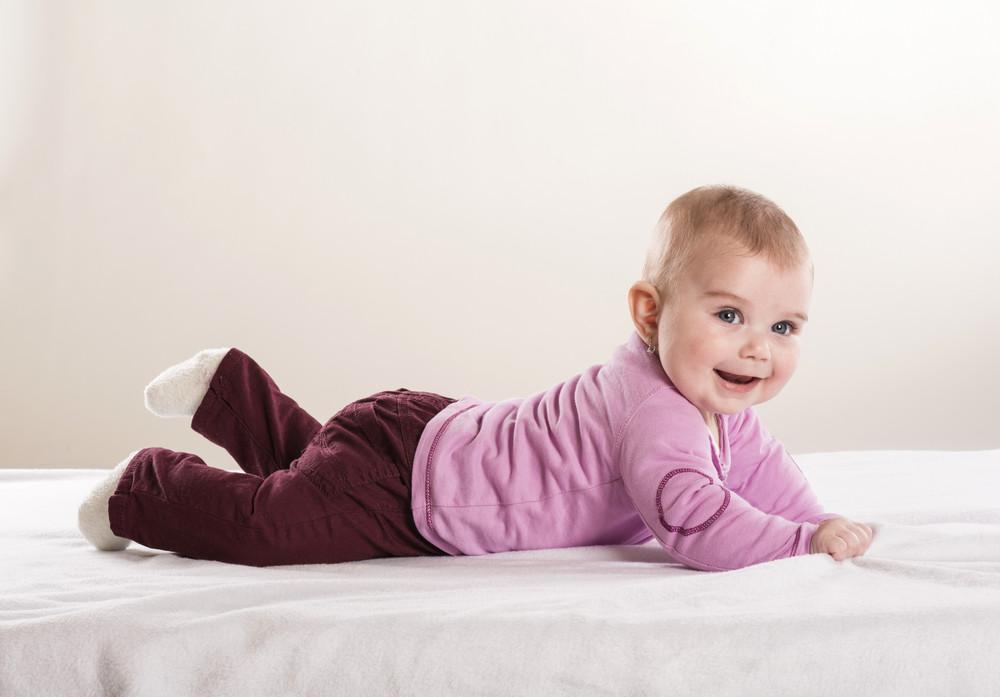 Sweet little baby is lying on mattress in studio