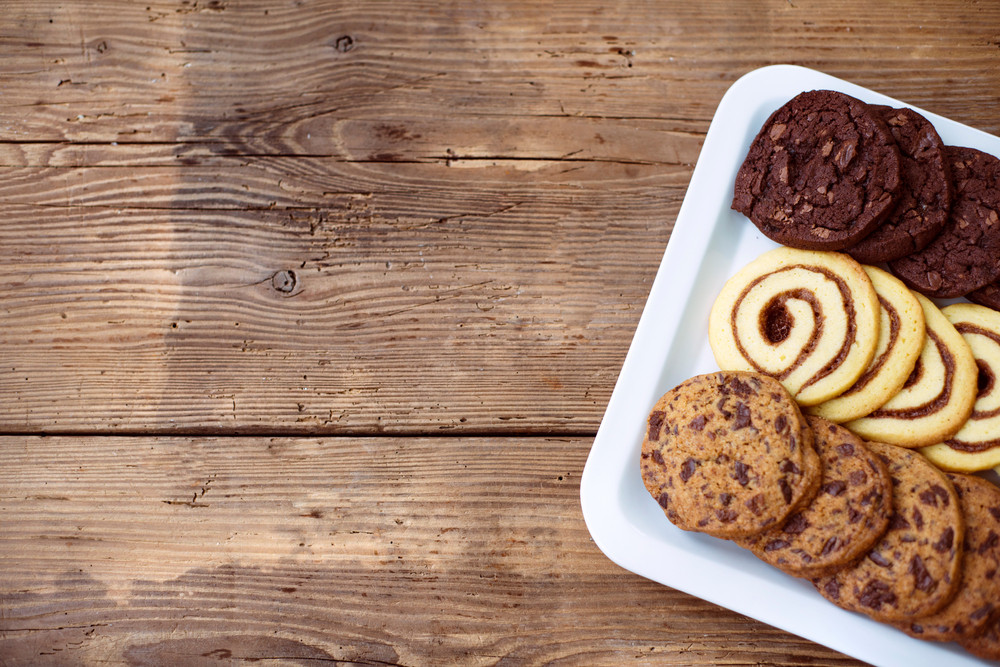 Table with various types of cookies on tray. Studio shot on brown wooden background. Copy space. Flat lay.