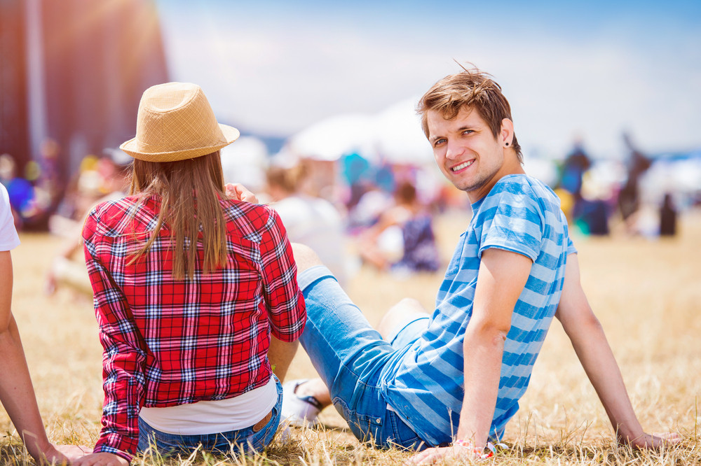 Teenage boy and girl at summer music festival, sitting on the grass in front of stage, rear view
