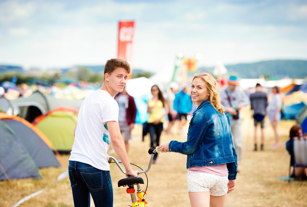 Teenage boy and girl in love with bike at summer music festival in a tent sector, back view, rear viewpoint