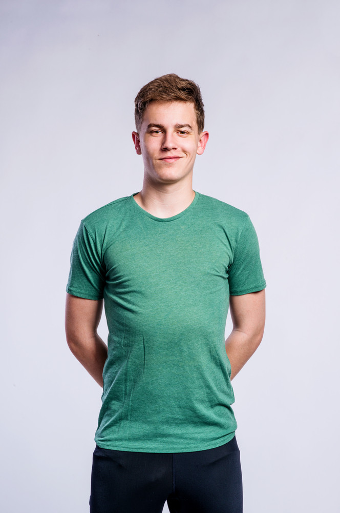 Teenage boy in black sports trousers and green t-shirt, young man, studio shot on gray background