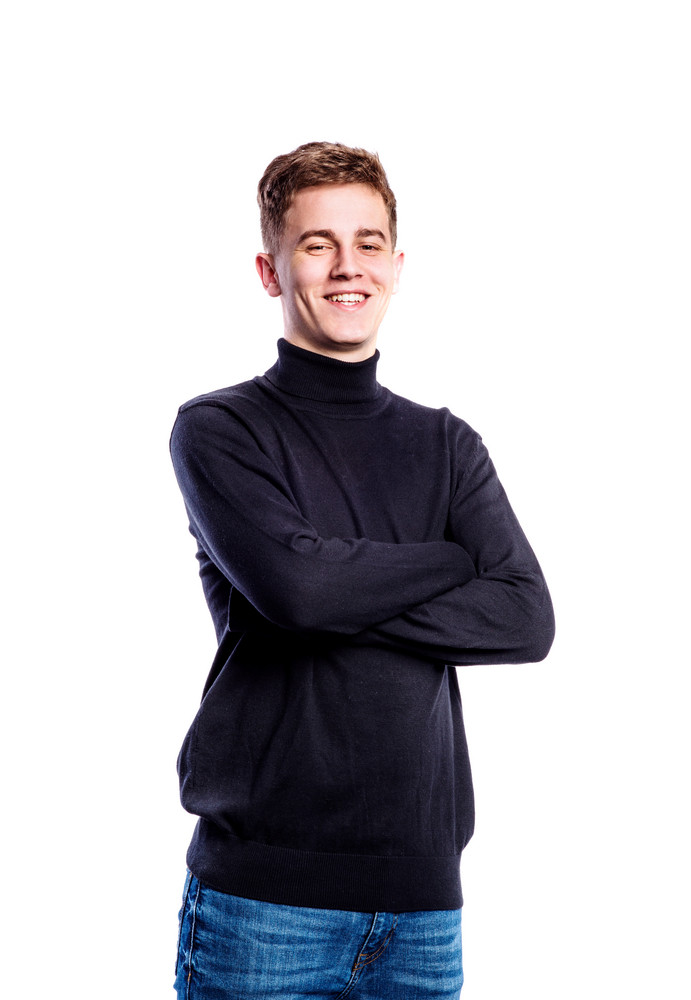 Teenage boy in jeans and black turtleneck sweater, young man, studio shot on white background, isolated