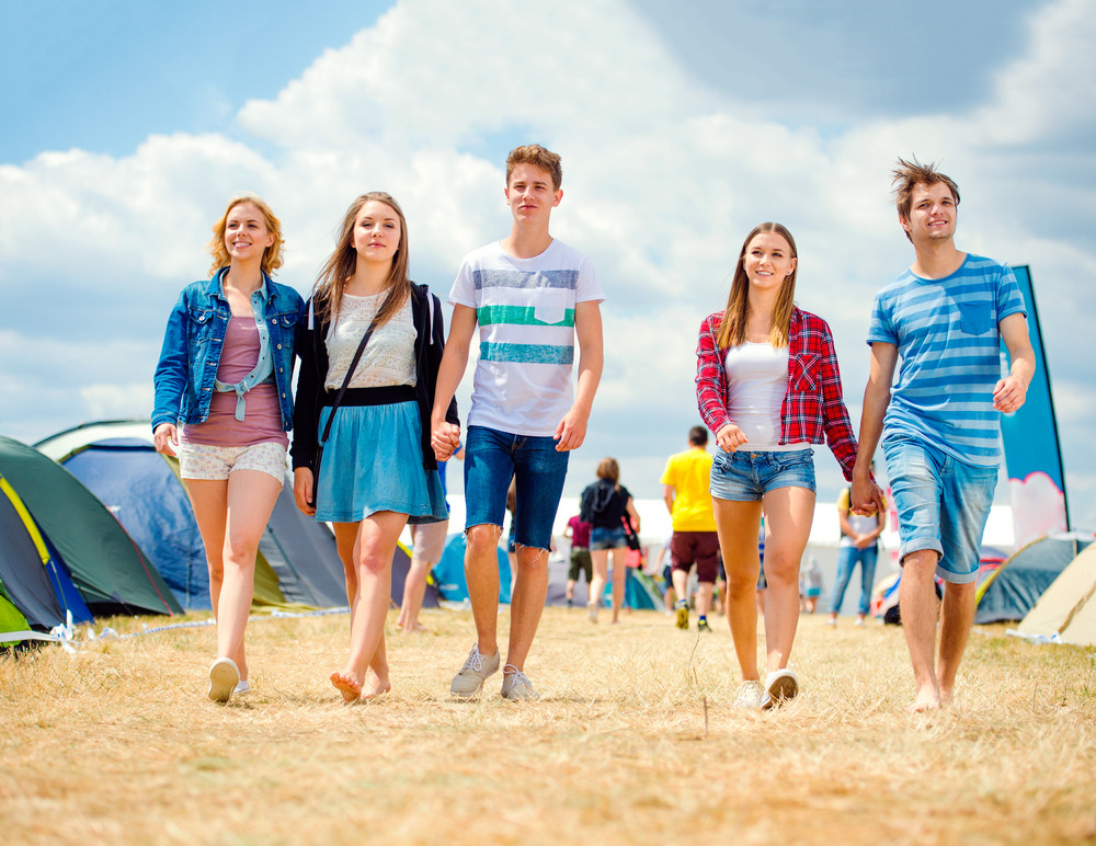 Teenage couples in love at tent music festival, sunny summer