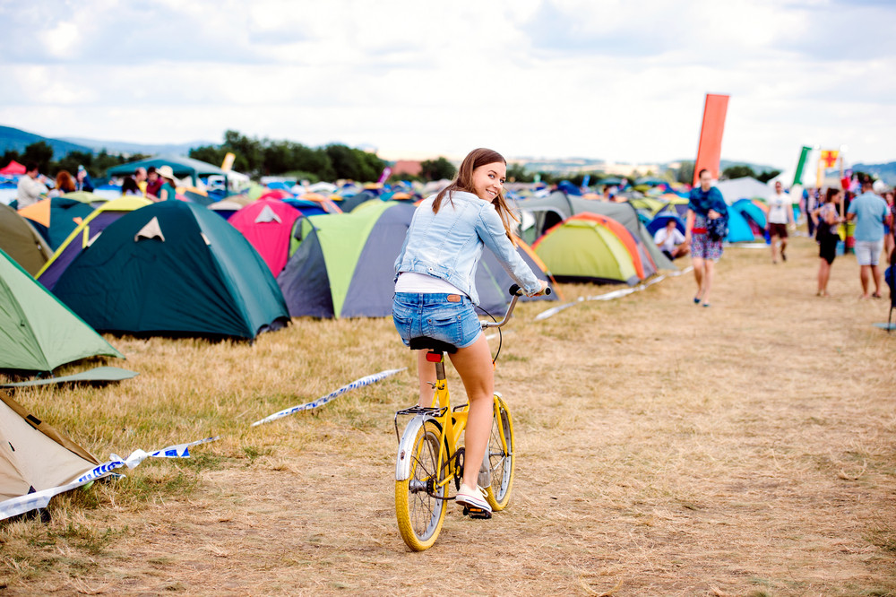 Teenage girl having fun riding yellow bike at summer music festival in a tent sector, back view, rear viewpoint