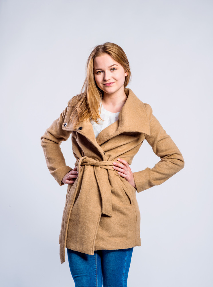Teenage girl in jeans and brown coat, young woman, studio shot on gray background