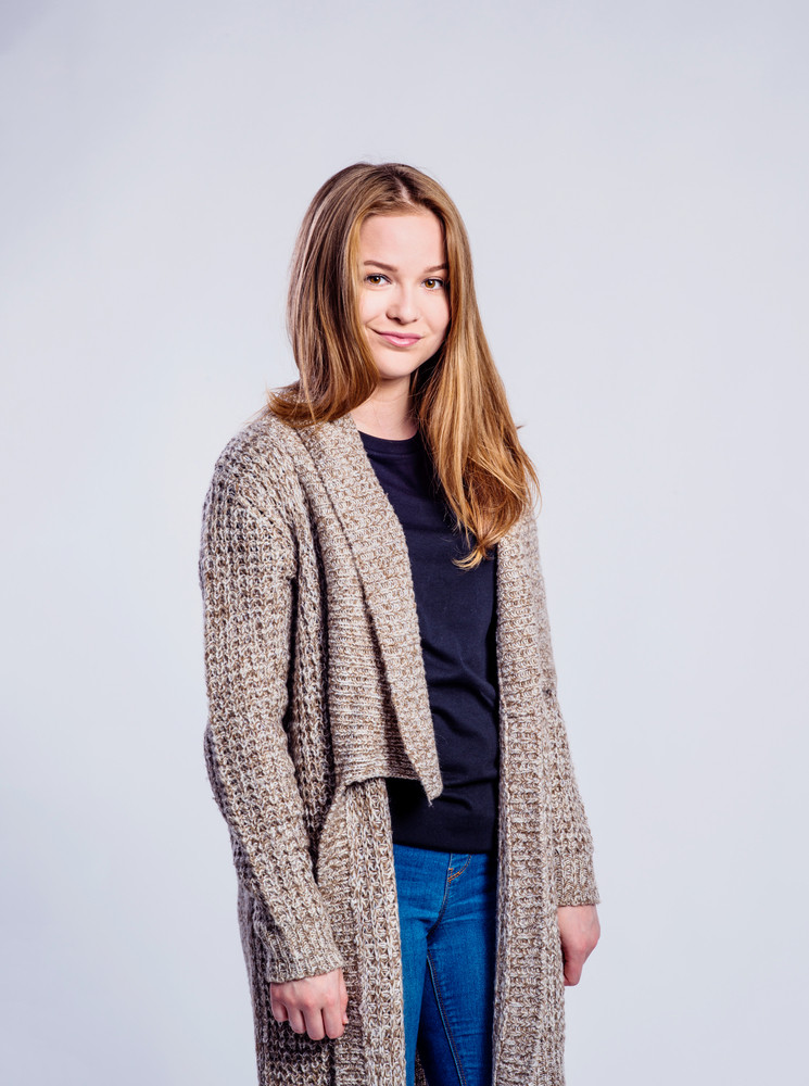 Teenage girl in jeans and long brown sweater, young woman, studio shot on gray background