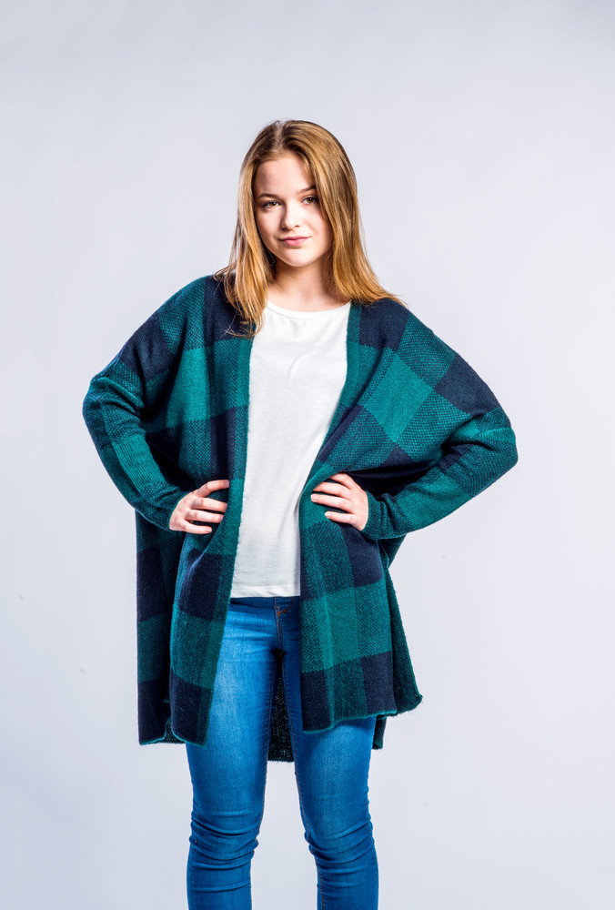 Teenage girl in jeans and long green checked sweater, young woman, studio shot on gray background